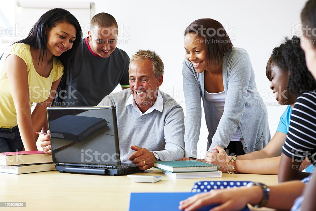 mature teacher and students looking at laptop in classroom royalty-free stock photo