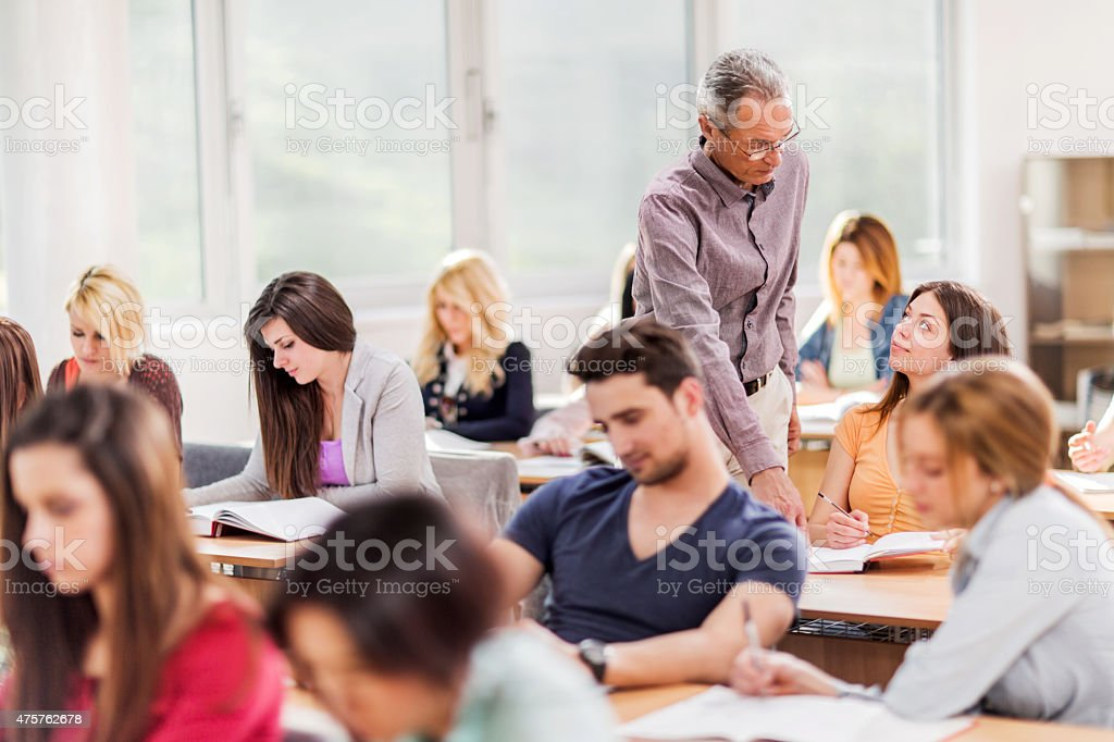 Mature teacher assisting female college student in the classroom. stock photo