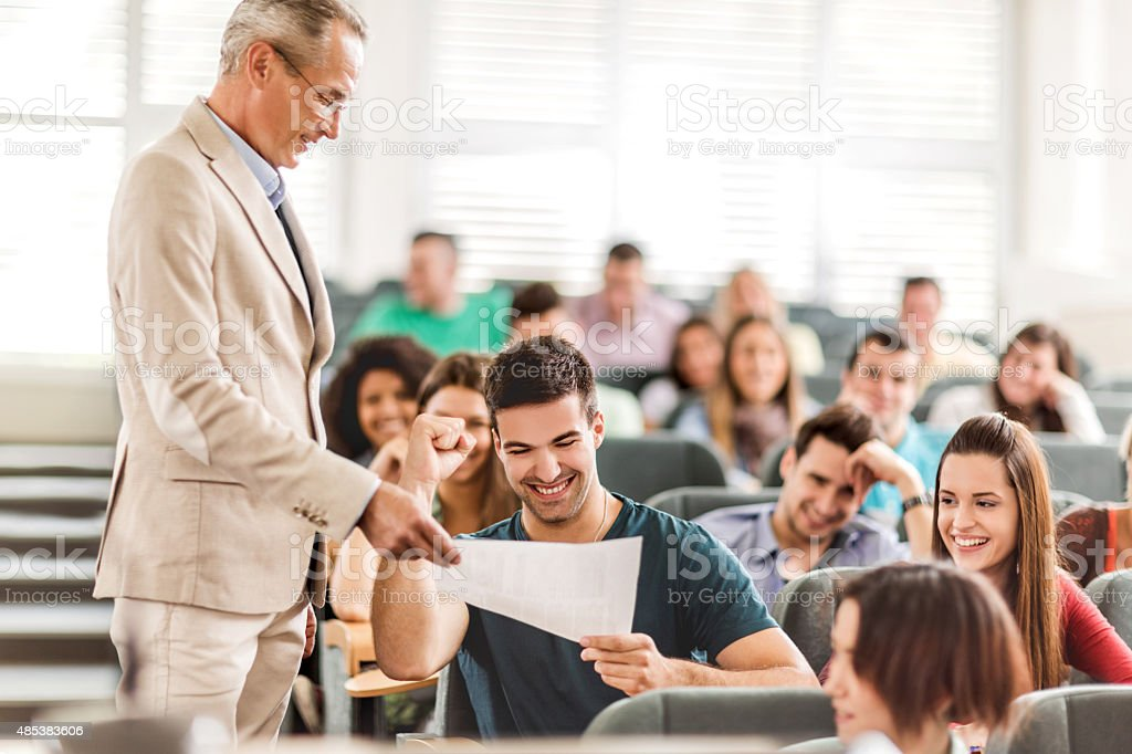 Mature teacher giving test results to cheerful student. stock photo