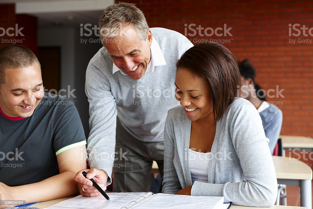 mature teacher helping students with their studies royalty-free stock photo