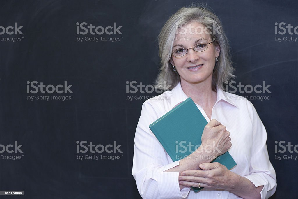 Mature teacher in white clutching notebook over blackboard royalty-free stock photo