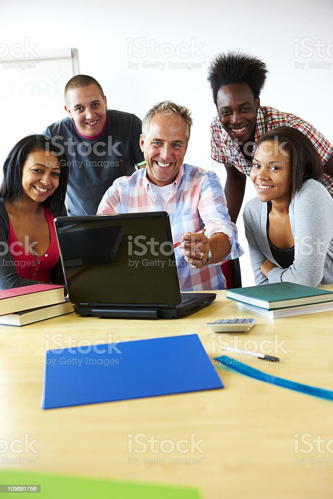 mature teacher looking at laptop with his students in classroom royalty-free stock photo