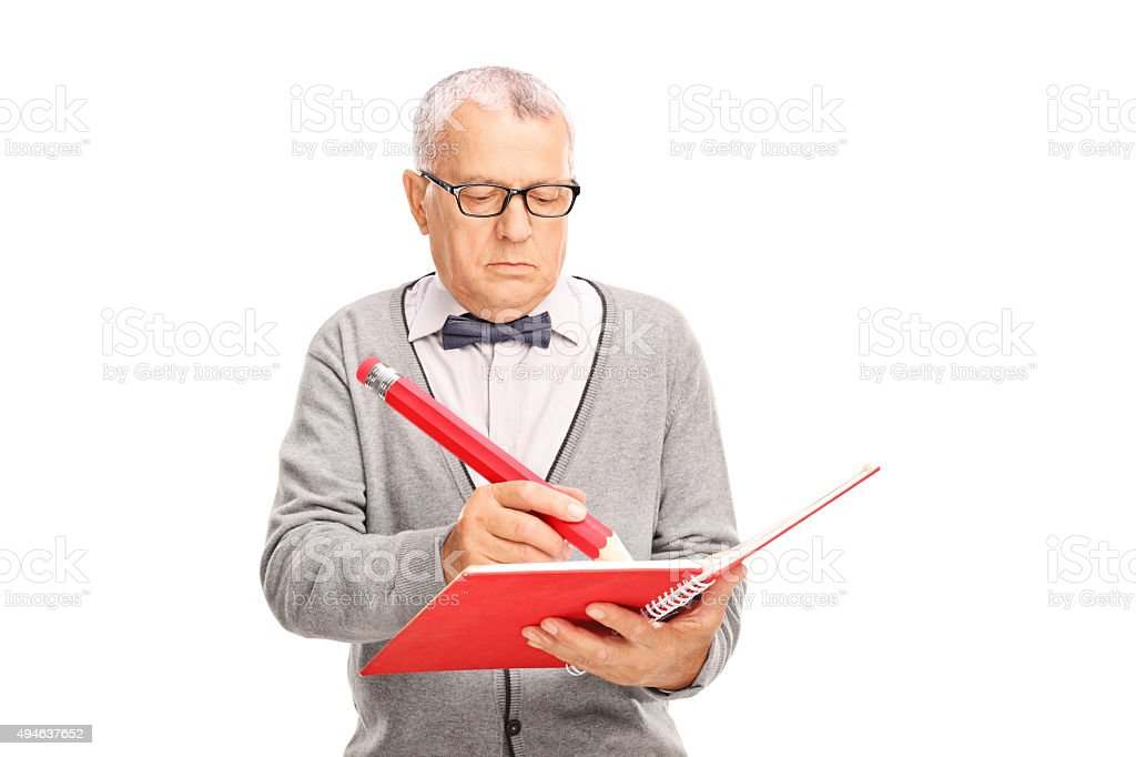 Mature teacher writing something in a notebook stock photo