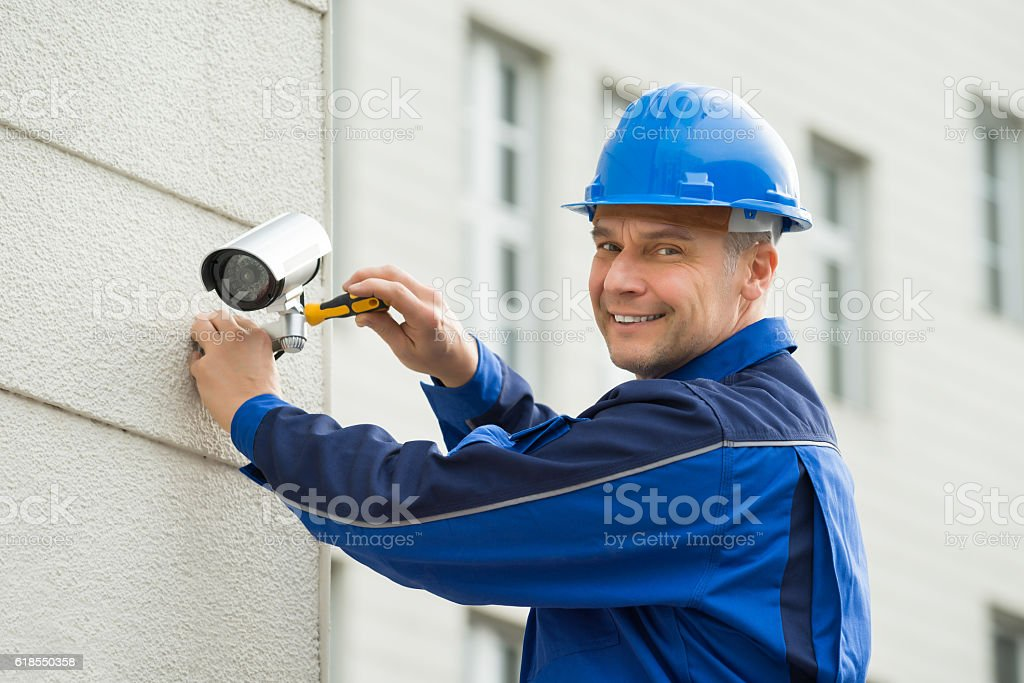 Mature Technician Installing Camera On Wall With Screwdriver stock photo