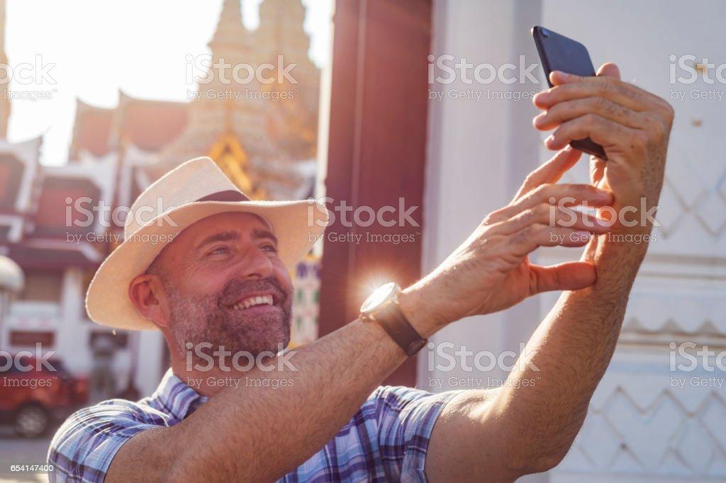 Mature Tourist Couple Taking Selfies At Bangkok Palace stock photo