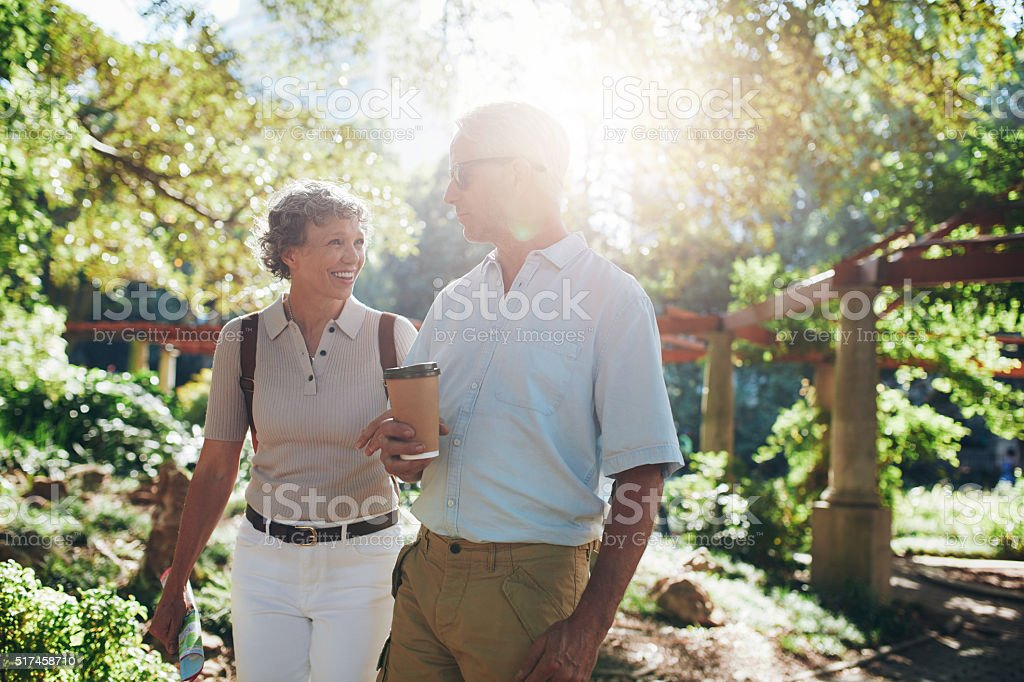 Mature tourist walking in a city park stock photo