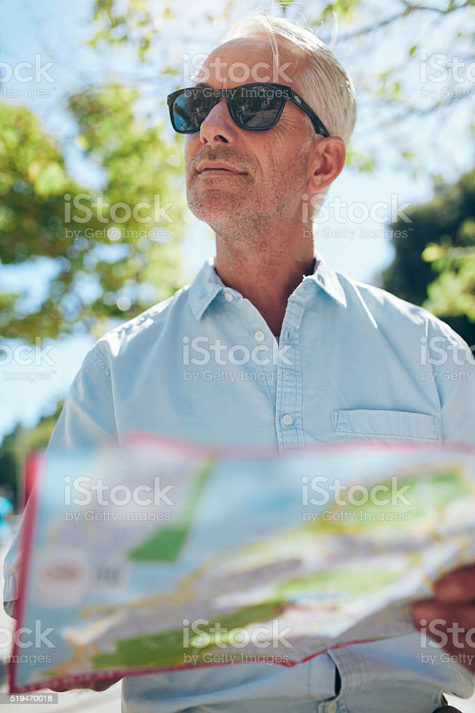 Mature tourist with a city map stock photo