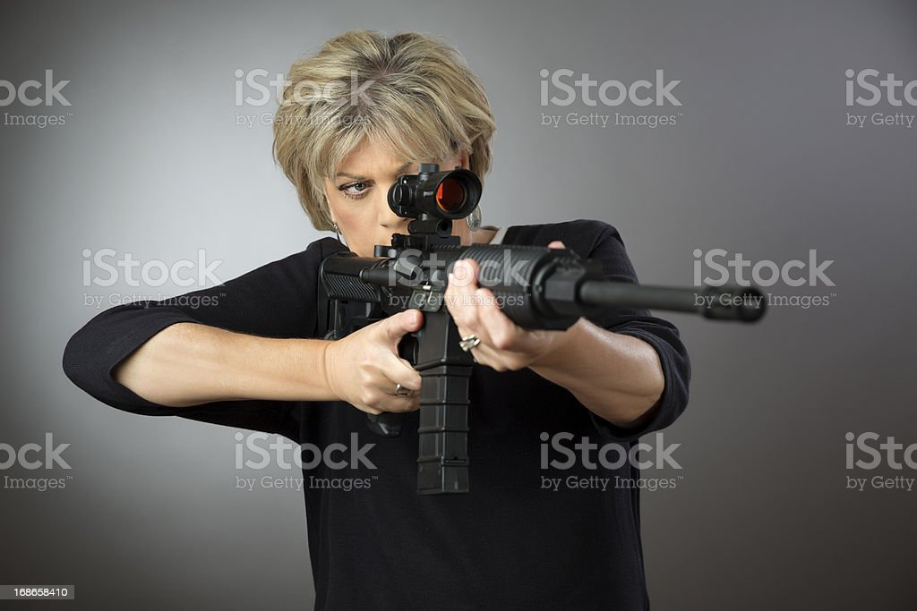 Mature woman aming a rifle on gray background stock photo