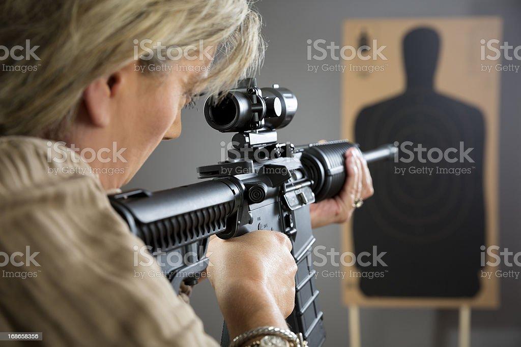 Mature woman aming rifle at a target royalty-free stock photo