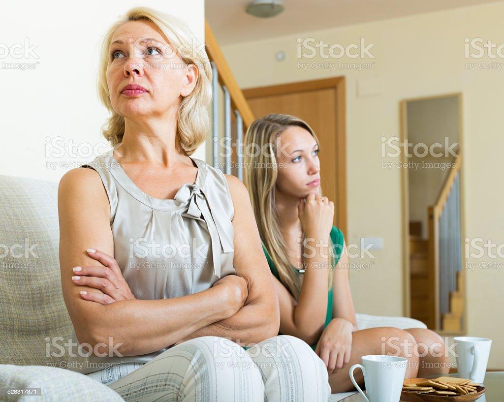 Mature woman and  adult daughter having quarrel stock photo