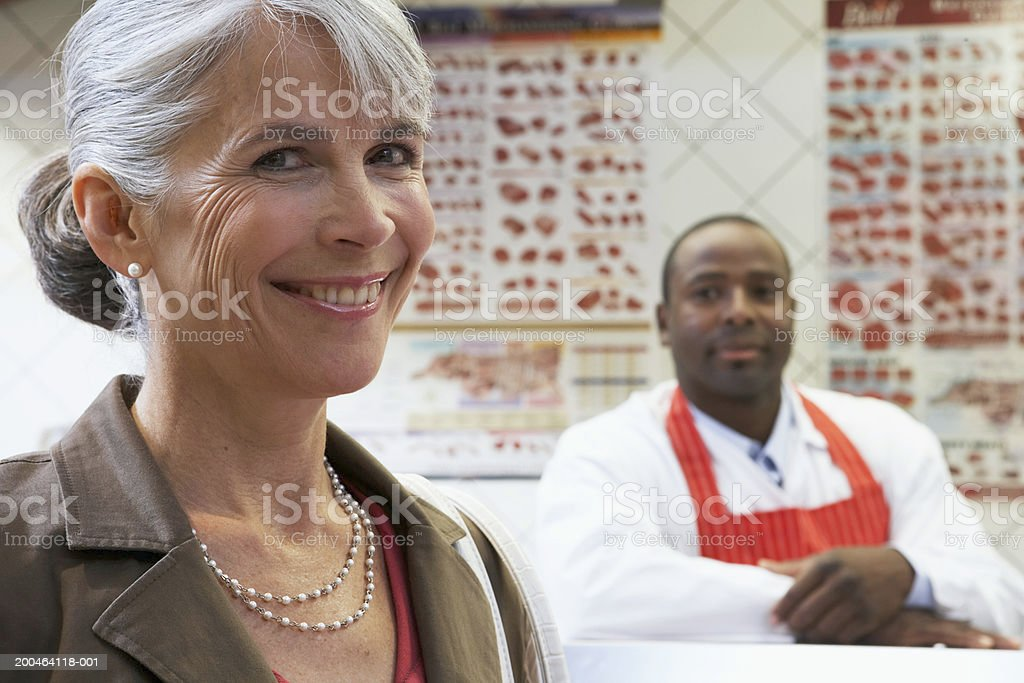Mature woman and butcher smiling, portrait, close-up (focus on woman) royalty-free stock photo