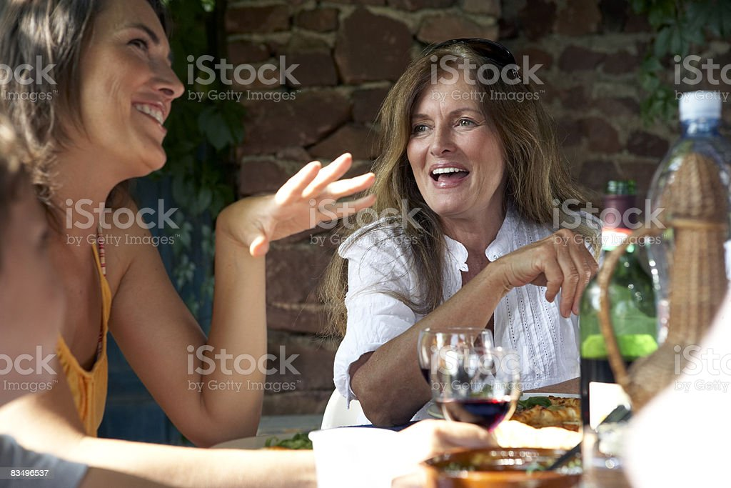mature woman and daughter eating lunch outdoors stock photo