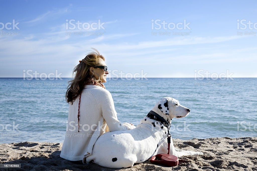 Mature woman and dog at the beach stock photo