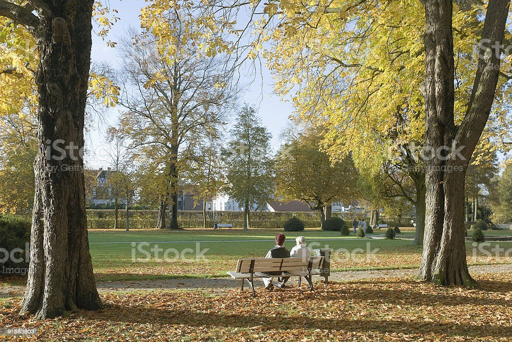 Mature woman and grandmother on park bench in autumn royalty-free stock photo