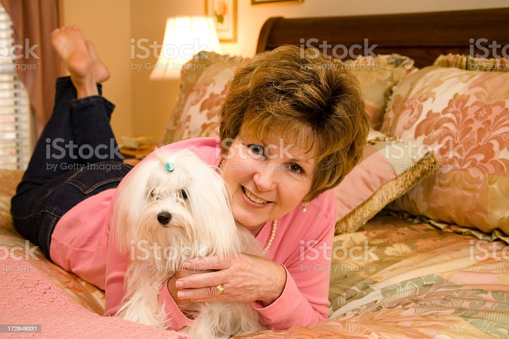Mature woman and her Maltese dog lying across  bed royalty-free stock photo