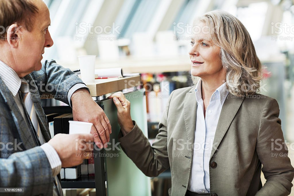 Mature woman and man talking in a library. stock photo