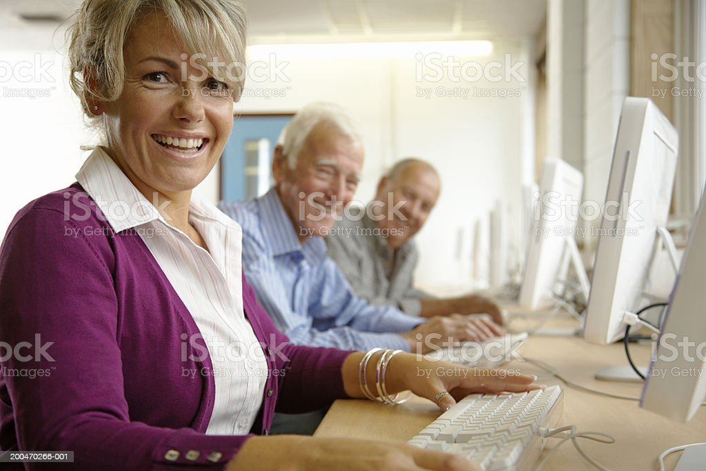 Mature woman and two mature men in computing class, portrait stock photo