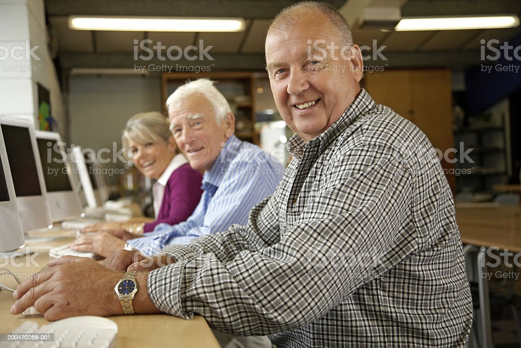 Mature woman and two mature men in computing class, portrait royalty-free stock photo