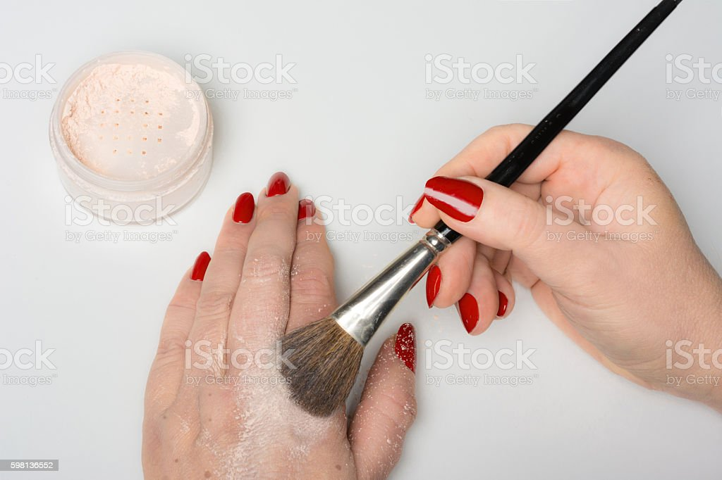 mature woman applies powder to hide her first age spots stock photo