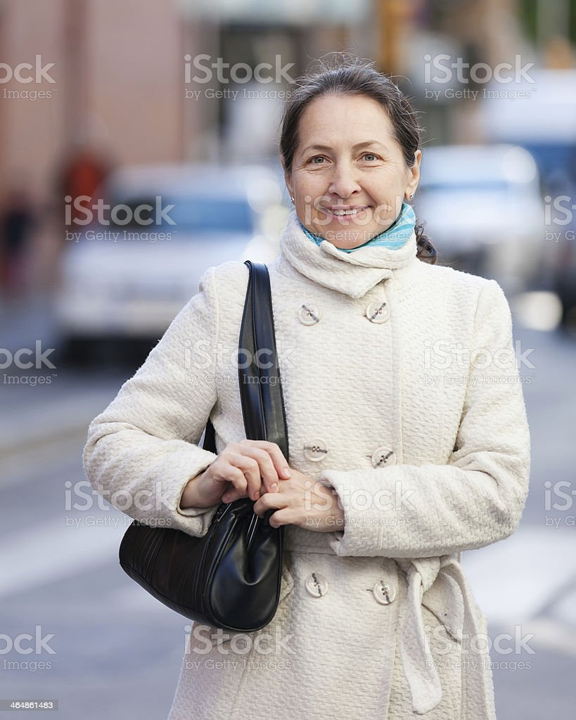 mature woman at city street in autumn stock photo