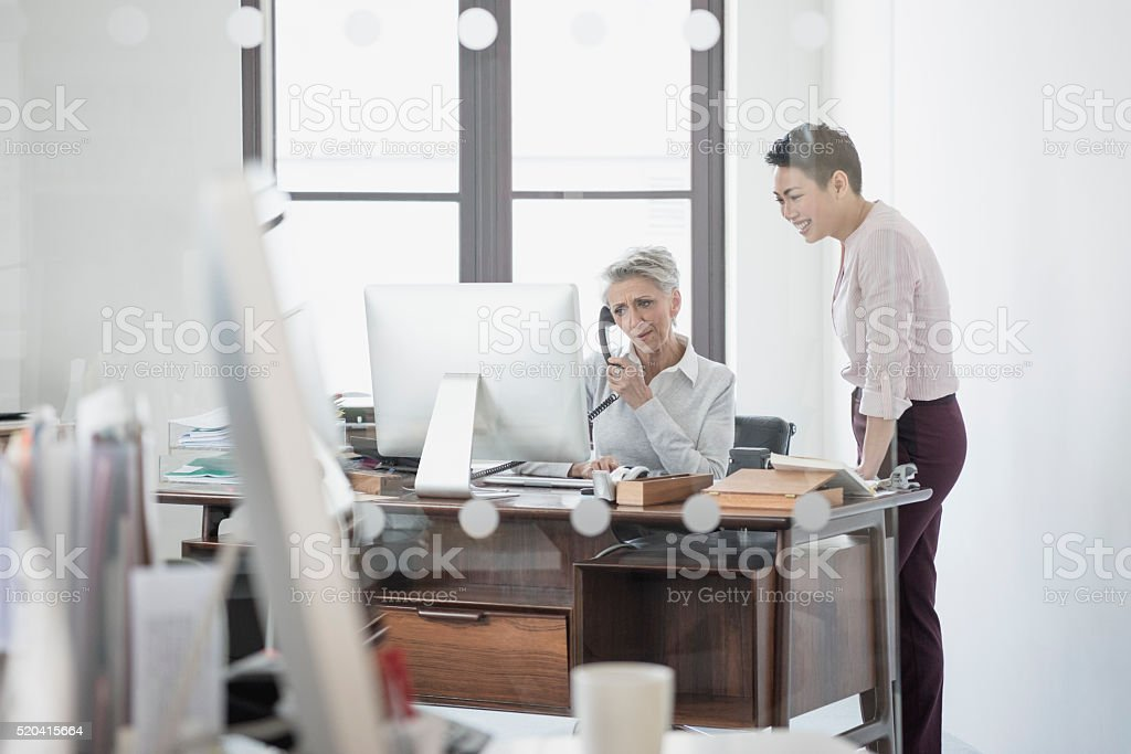 Mature woman at desk on phone with female colleague stock photo