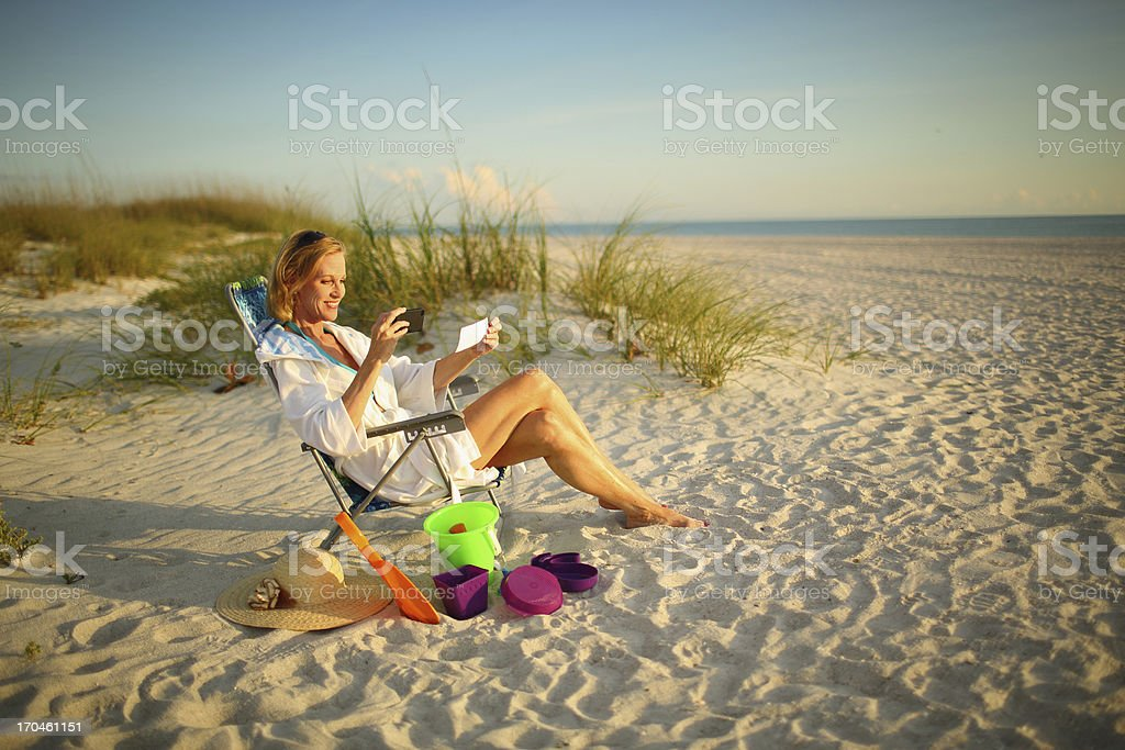 Mature woman at the beach depositing a check with phone stock photo