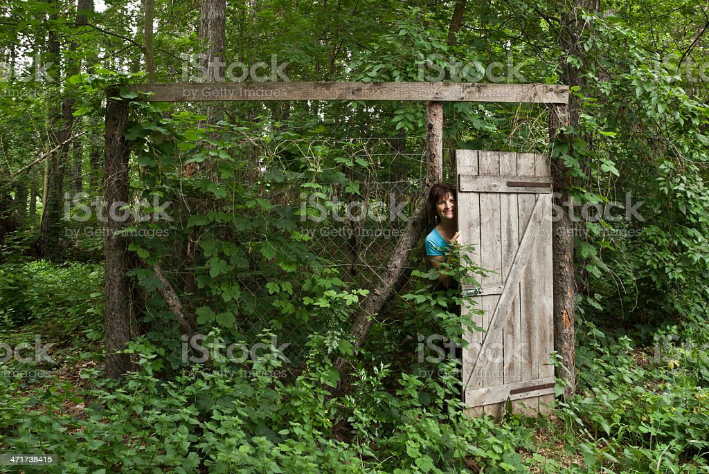 Mature woman behind wooden door. stock photo