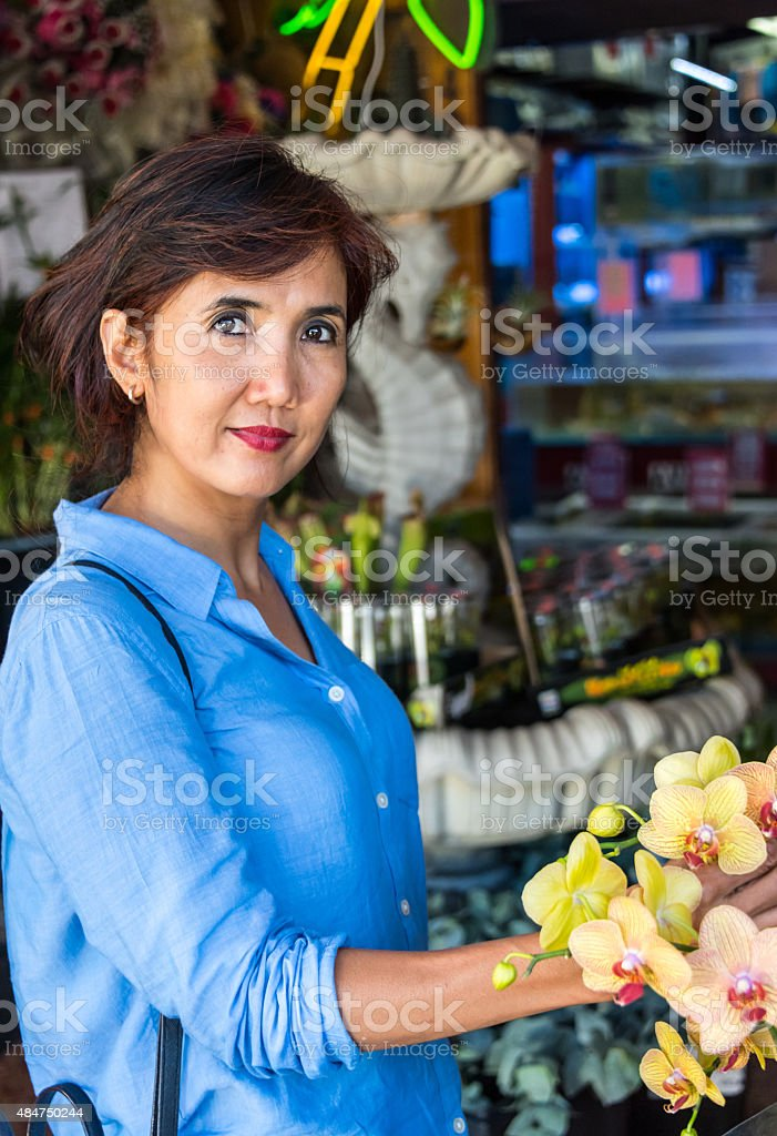 Mature woman buying flowers stock photo