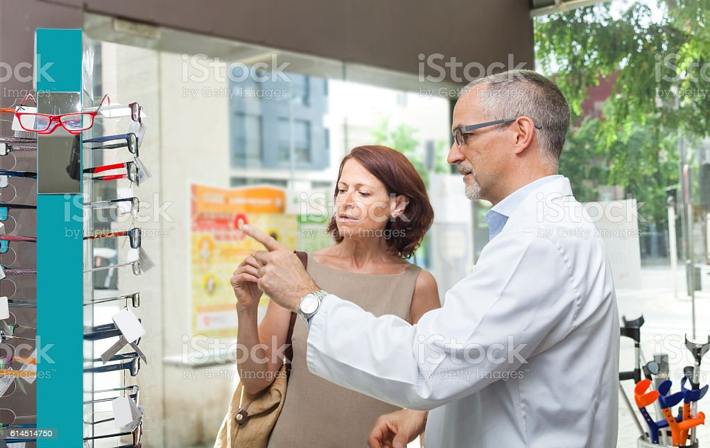 Mature woman buying glasses at the optic or pharmacy stock photo