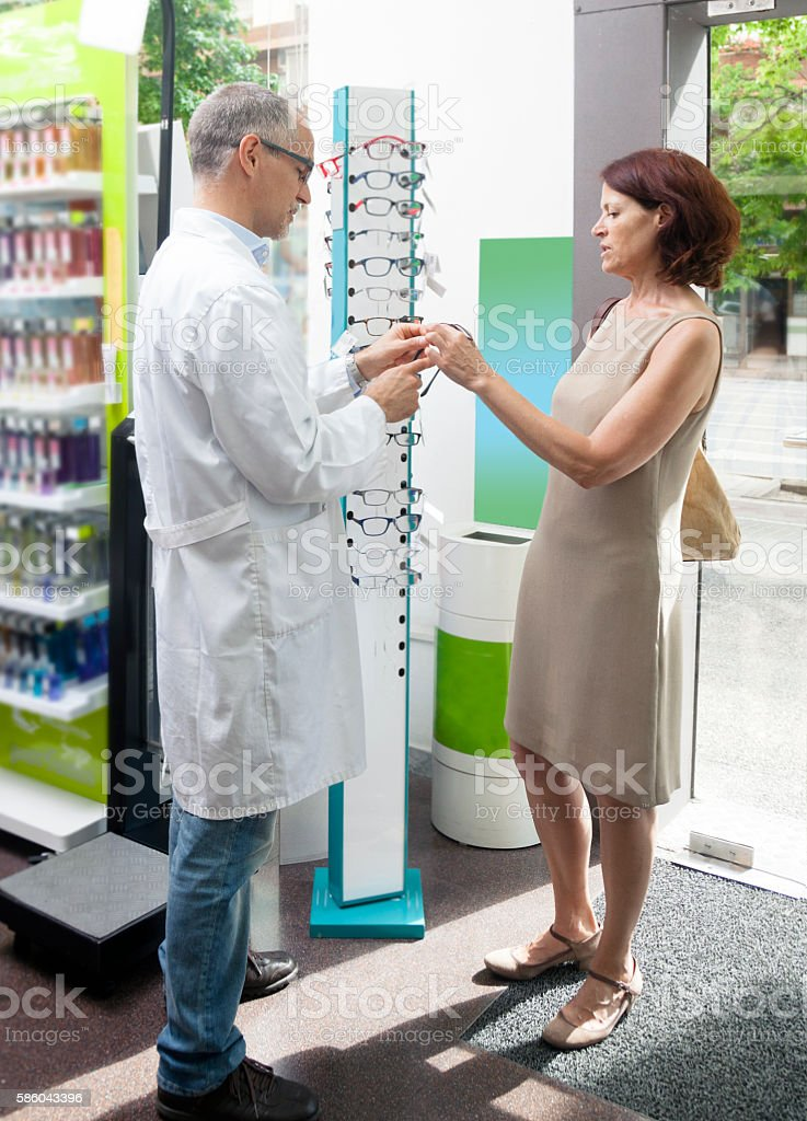 Mature woman buying glasses stock photo