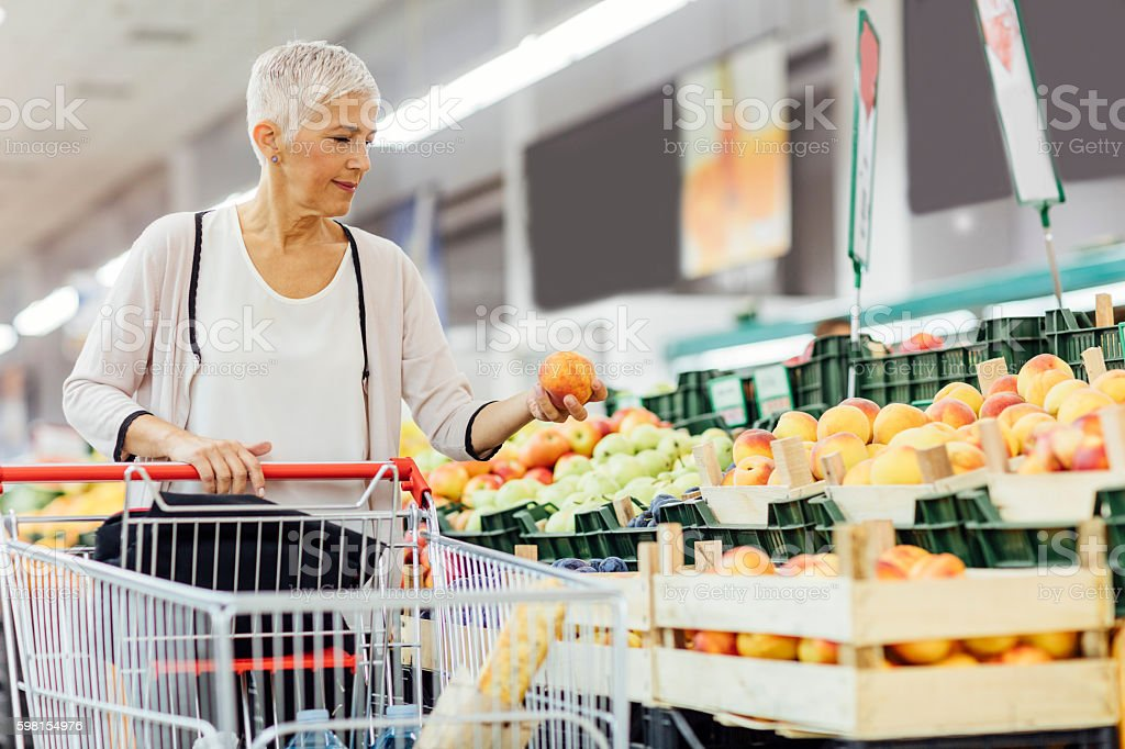 Mature Woman Buying Organic Fruits In Local Supermarket. stock photo