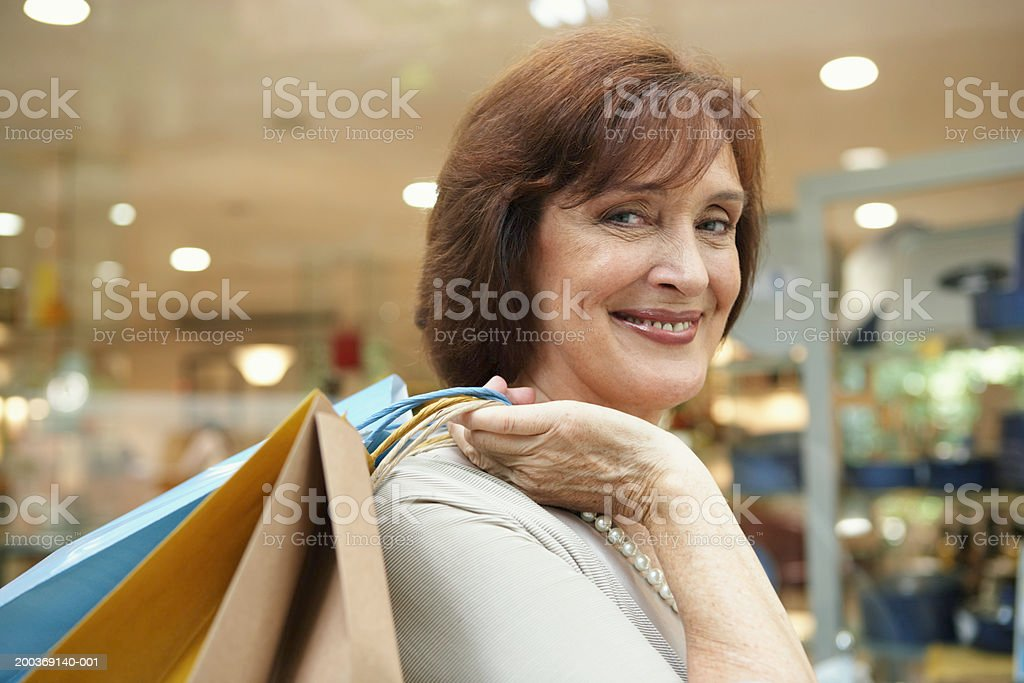 Mature woman carrying shopping bags over shoulder, smiling, portrait stock photo