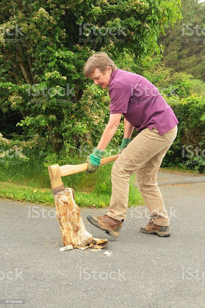 mature woman chopping wood with long-handled axe royalty-free stock photo