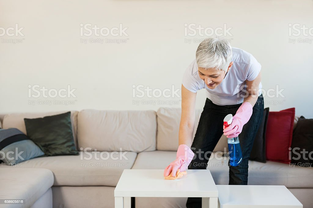 Mature woman cleaning home stock photo