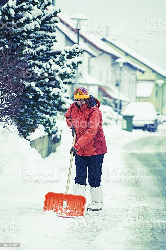 Mature woman cleaning snow in front of her house royalty-free stock photo