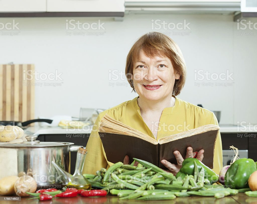 mature woman cooking  with  cookery book royalty-free stock photo