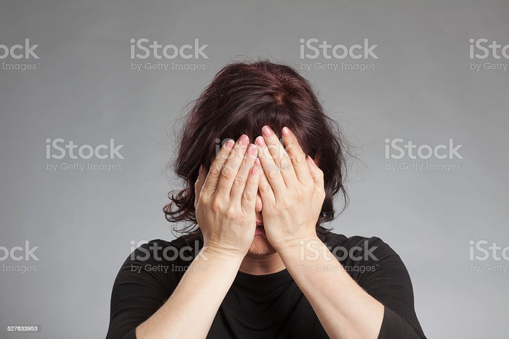 Mature woman covering eyes stock photo