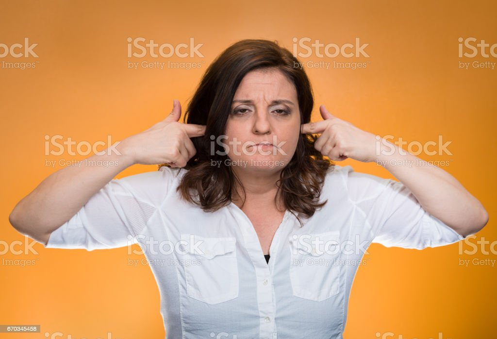 mature woman covering plugging ears annoyed by loud noise ignoring someone stock photo
