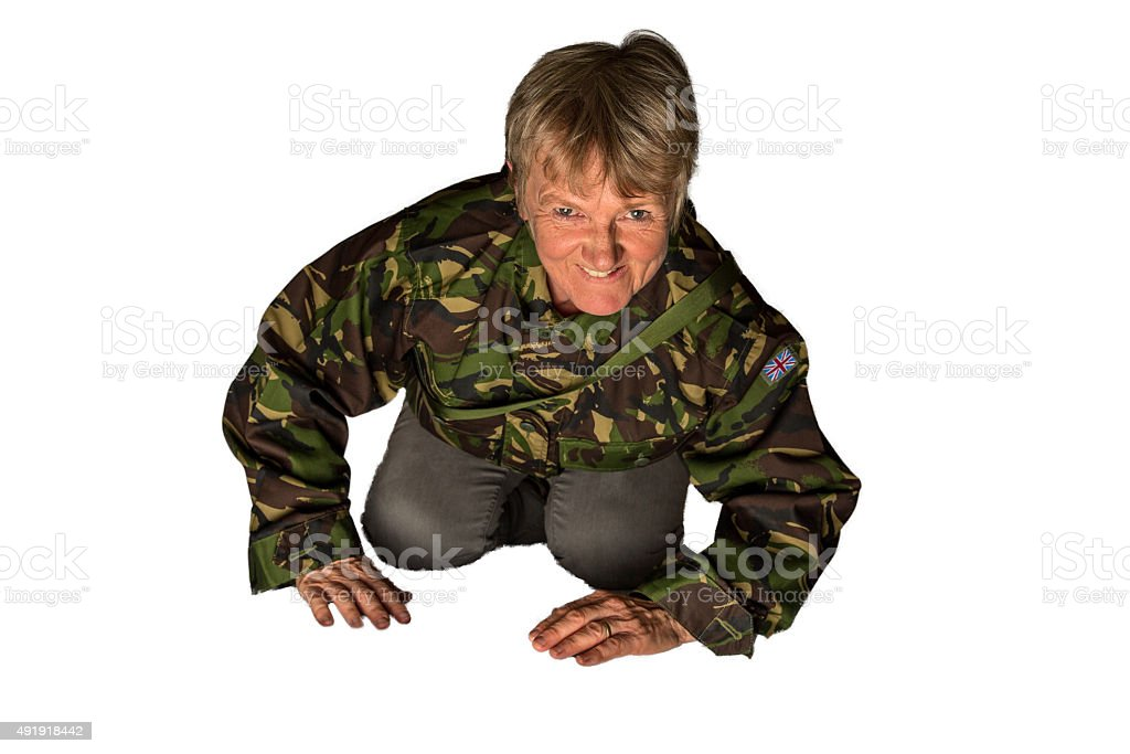 Mature woman crawling on all fours wearing army fatigues stock photo