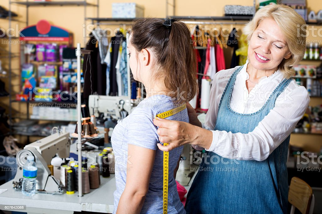 Mature woman customer getting measured by tailor stock photo
