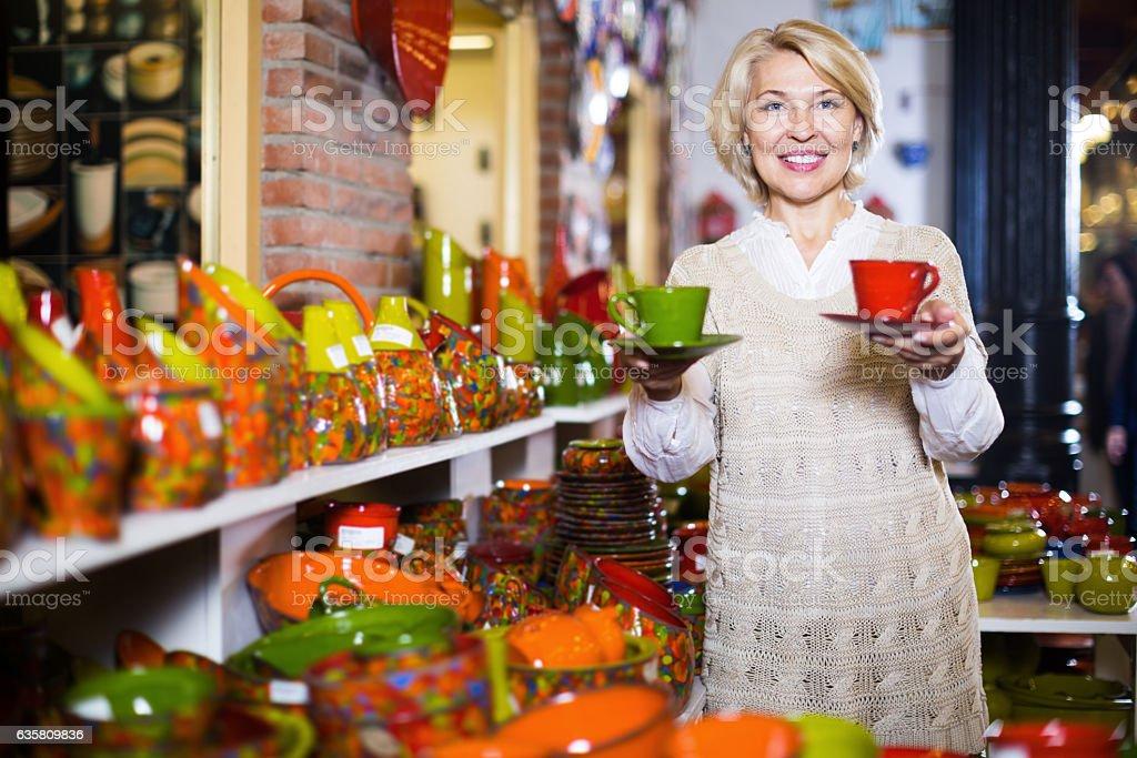 Mature woman customer holding  ceramic cups stock photo