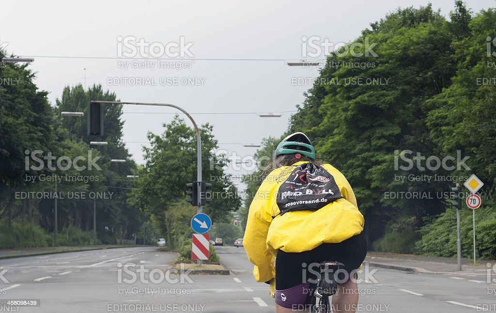 Mature woman cycling on multiple lane highway royalty-free stock photo