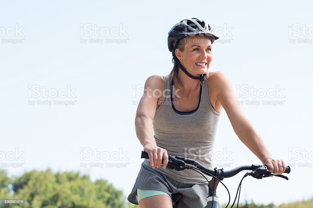 Mature woman cycling stock photo
