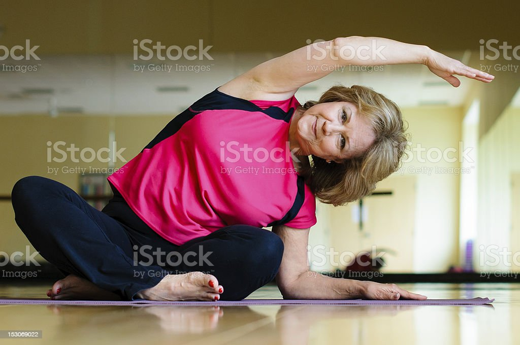 Mature Woman Does Yoga Side Bend stock photo