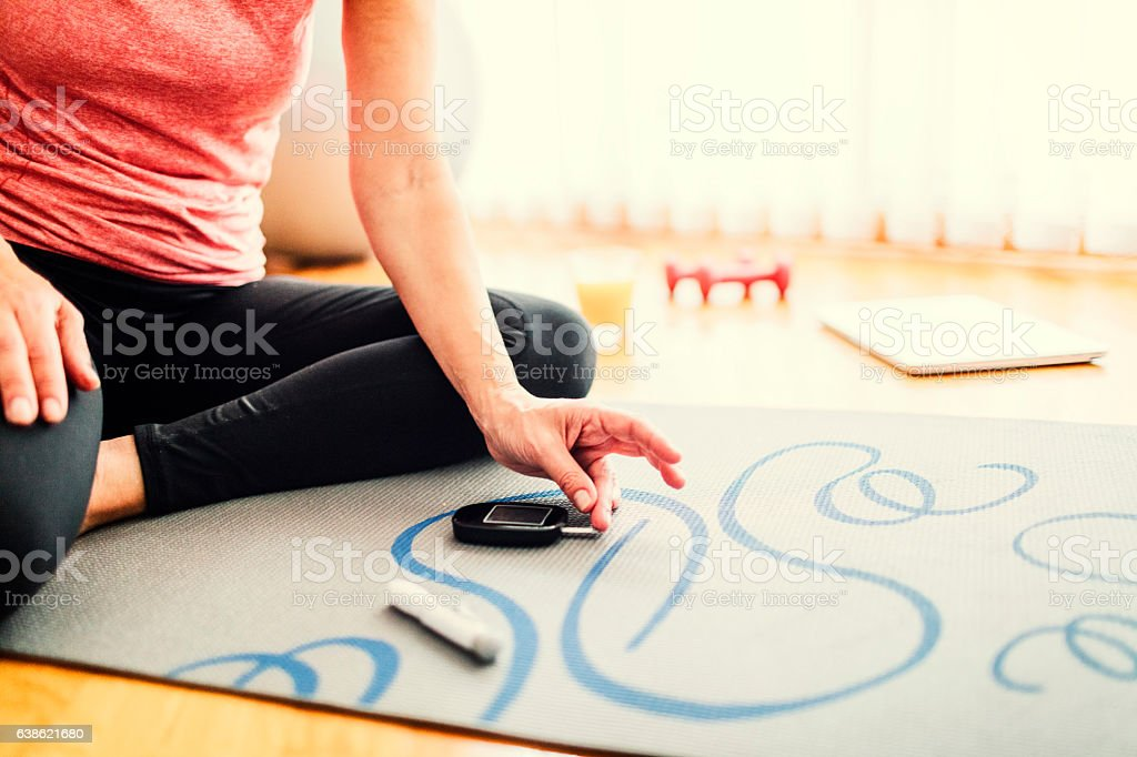 Mature Woman Doing Blood Sugar Test after exercise. stock photo