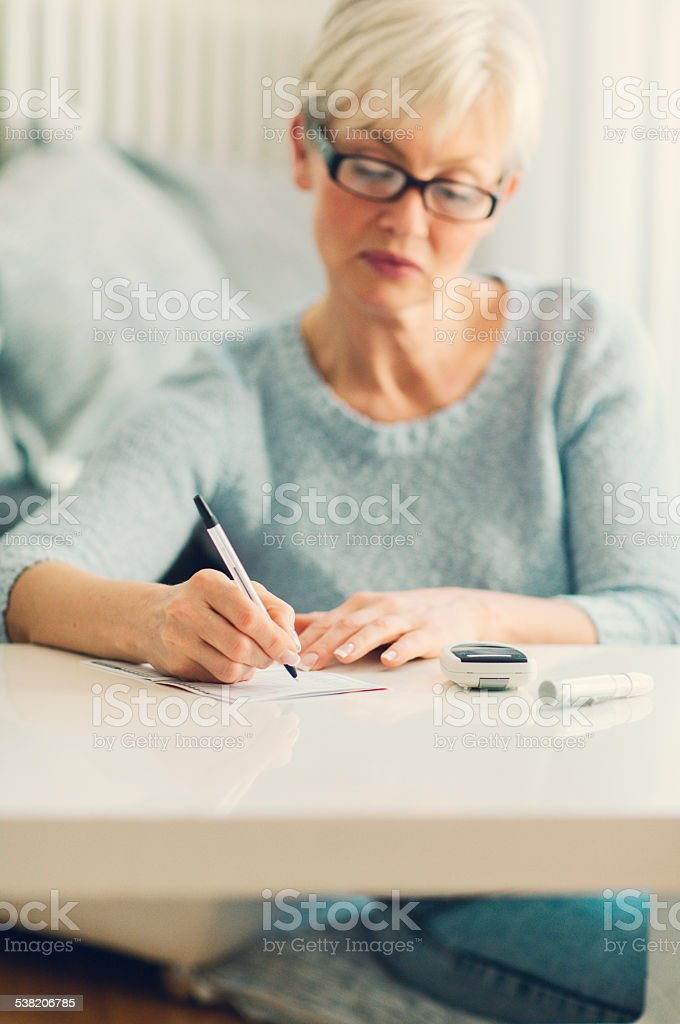 Mature Woman Doing Blood Sugar Test at home. stock photo