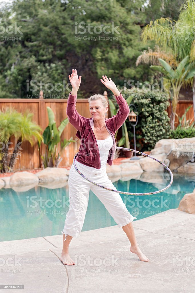 Mature woman doing hula hoop stock photo