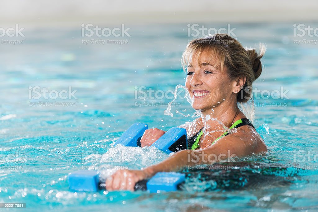 Mature woman doing water aerobics with dumbbells stock photo