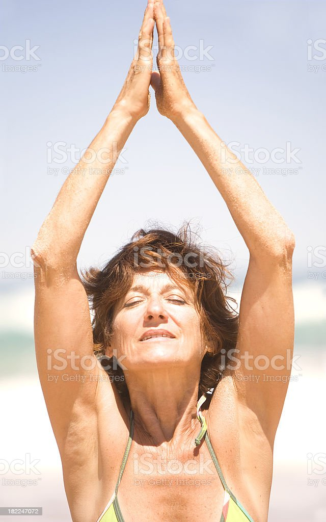 Mature Woman Doing Yoga and Relaxing on the Beach royalty-free stock photo