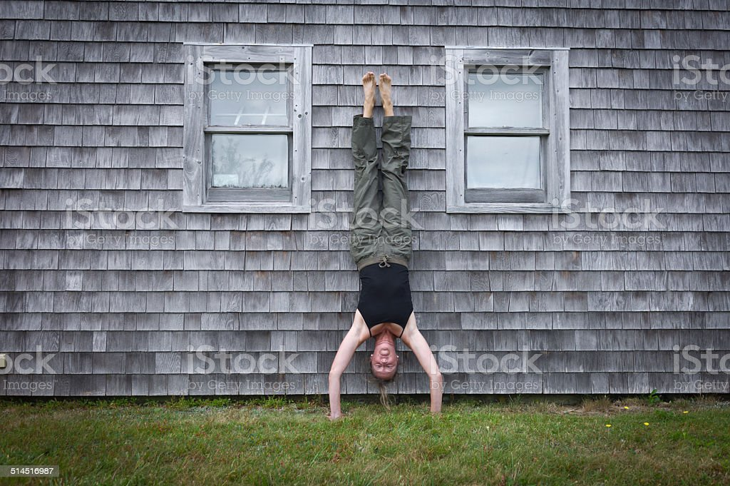 Mature Woman Doing Yoga Handstand Against an Old Building. stock photo